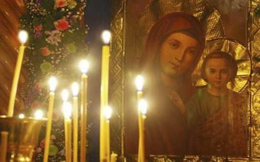 Горящие свечи перед иконой Божьей Матери
