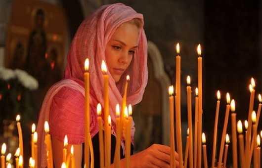 Верующая устанавливает церковную свечу в храме